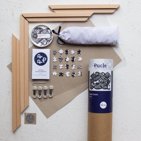 Tubus od Pucle s motívom od Lukáša Cehľára. V balení nájdete puzzle schované v bavlnenom vrecúšku, drevený rám, spodnú podložku, ochrannú fóliu, príručku bystrých skladačov a spájacie komponenty